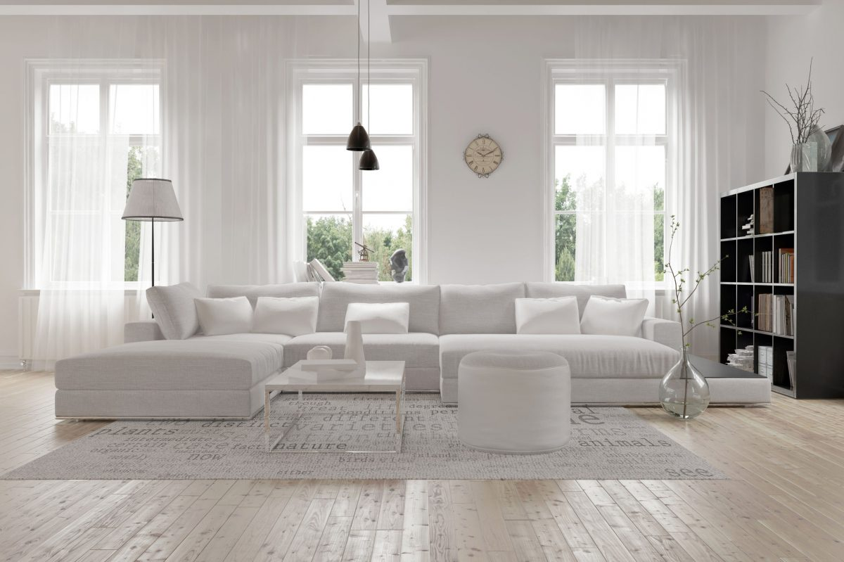 38112668 - modern spacious lounge or living room interior with monochromatic white furniture and decor below three tall bright windows with a dark bookcase accent in the corner