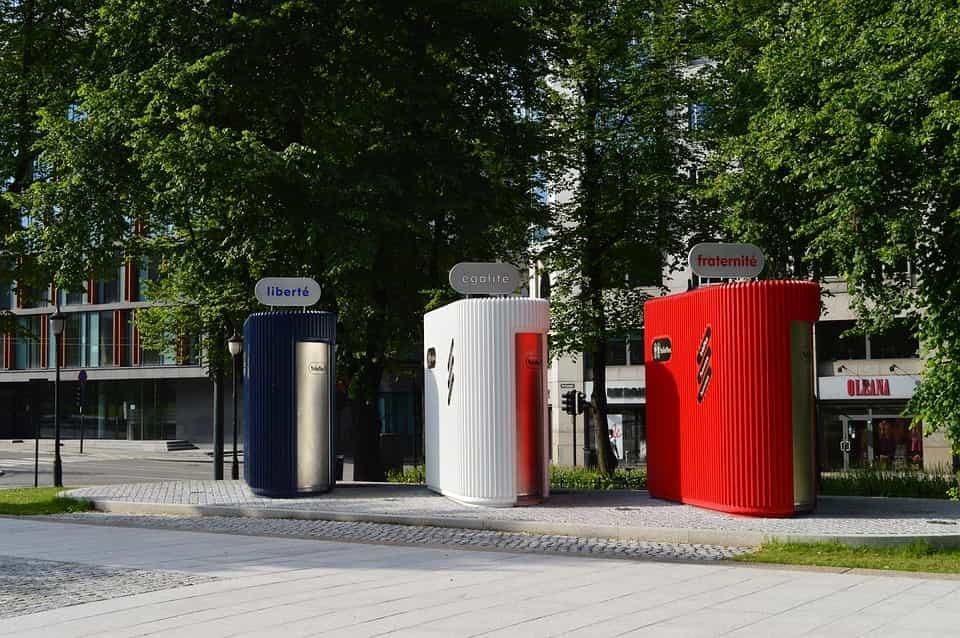 Toilettes publiques de type sanisette dans un parc, peintes en bleu, blanc et rouge.